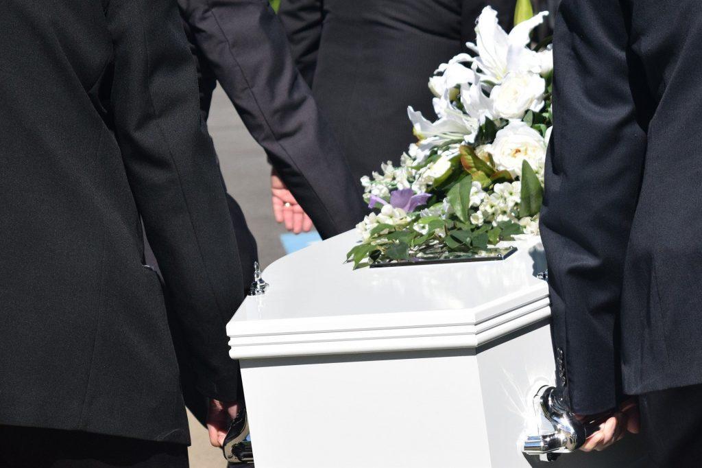 Personnes portant un cercueil blanc
